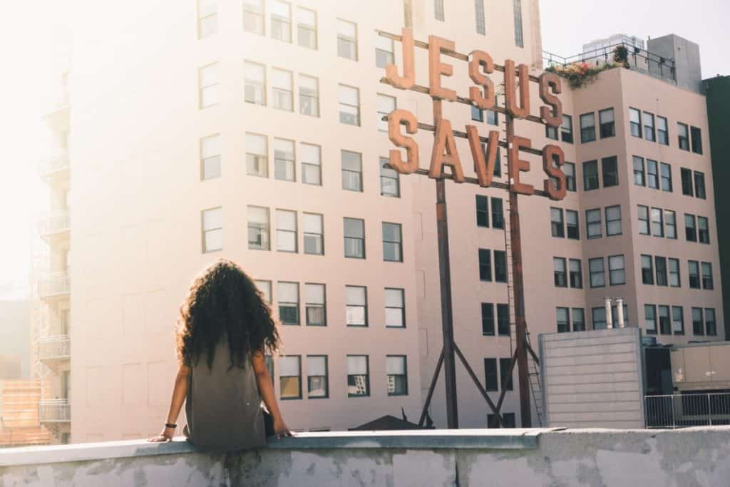 Woman sitting on a roof with a sign that says: Jesus Saves